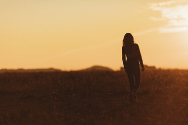 Woman walking in nature at sunset - JPF00365