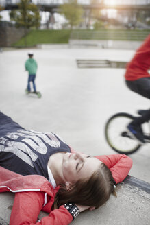 Teenage girl lying on a wall at a skatepark - RORF01823
