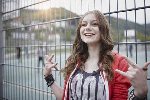 Portrait of a happy teenage girl gesturing at a fence at a sports field - RORF01826