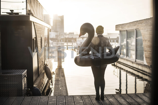 Businesswoman with floating swan standing on a houseboat, looking at distance - MJRF00085