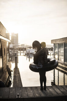 Businesswoman with floating swan standing on a houseboat, looking at distance - MJRF00088