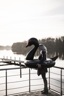 Businesswoman with floating swan standing on a houseboat - MJRF00094