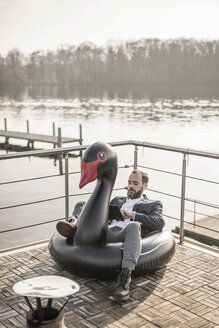 Hip businessman working on a houseboat, sitting a floating swan, using digital tablet - MJRF00106