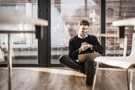 Businessman sitting on floor of his office, using laptop and smartwatch - MJRF00112