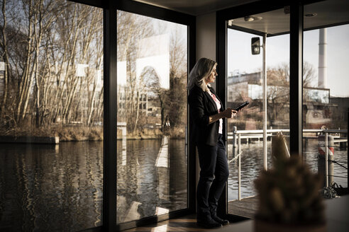 Businesswoman standing on a houseboat, using digital tabet - MJRF00121