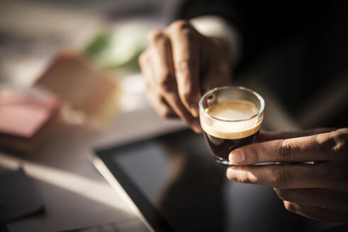 Businessman holding cup of coffee in his office - MJRF00124