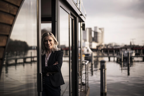 Businesswoman standing on a houseboat, looking out of window - MJRF00142