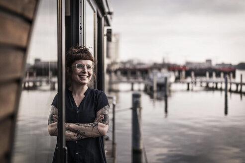 Woman leaning in window of a houseboat, taking a break - MJRF00145