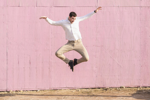 Exuberant young man jumping in front of pink wall - UUF16748