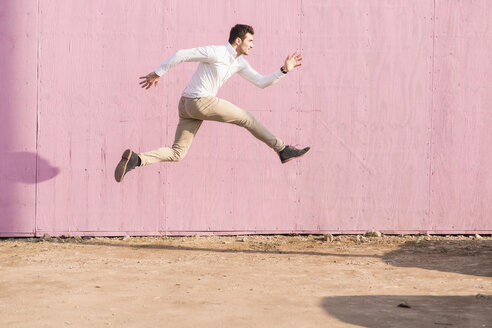 Exuberant young man jumping in front of pink wall - UUF16751