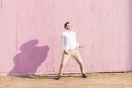 Exuberant young man listening to music in front of pink wall - UUF16754