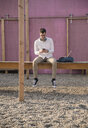 Young man sitting on platform using cell phone - UUF16766