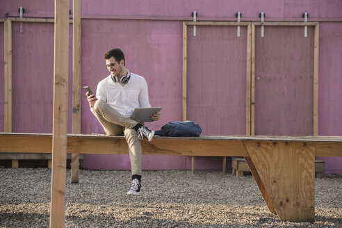 Smiling young man sitting on platform using cell phone - UUF16769