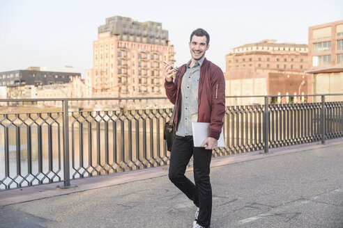Happy young man with tablet, cell phone and bag on a bridge in the city - UUF16796