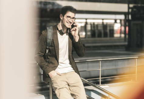 Smiling young man talking on cell phone at the station - UUF16814