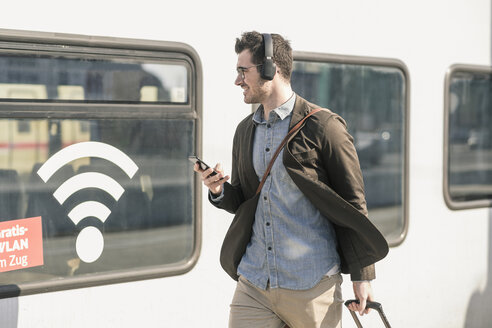 Smiling young man with headphones and cell walking along train with wifi symbol - UUF16820
