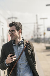 Smiling young man with cell phone at station platform - UUF16823