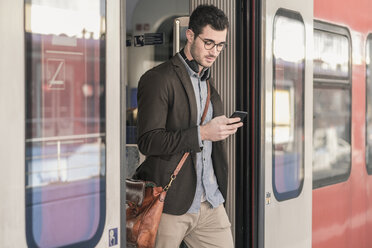Young man using cell phone in commuter train - UUF16826