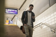 Smiling young man with cell phone walking down stairs at the station - UUF16841