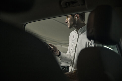 Young man with cell phone, earphones and bag at a car - UUF16847