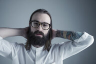 Portrait confident brunette Caucasian young man with beard and arm tattoo with hands behind head - HEROF30194