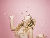 Playful young woman with long curly blonde hair throwing confetti overhead against pink background - HEROF30218