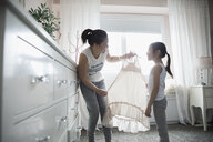 Mother and daughter looking at dress in bedroom - HEROF30299