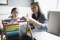 Mother home schooling daughter using abacus at dining table - HEROF30311