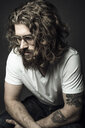 Thoughtful handsome young man with curly hair and tattoos - HEROF30362