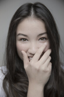 Portrait beautiful brunette teenage girl with brown eyes laughing with hand over mouth - HEROF30371