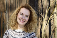 Blonde woman with curly hair smiling, norwegian sweater - ECPF00606