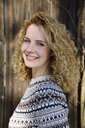 Blonde woman with curly hair smiling, norwegian sweater - ECPF00609