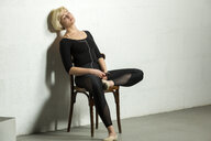 Portrait of blond woman wearing black unitard sitting on chair listening music with earphones - VGF00248