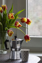 Espresso can and mug on a table with bouquet of tulips in the background - MELF00203