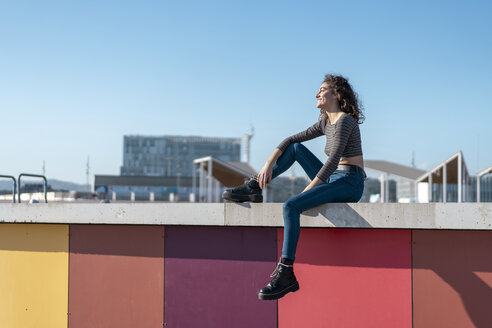 Young woman siiting on a wall, looking over city - AFVF02605