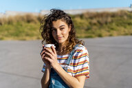 Young woman drinking coffee from a disposable cup - AFVF02611