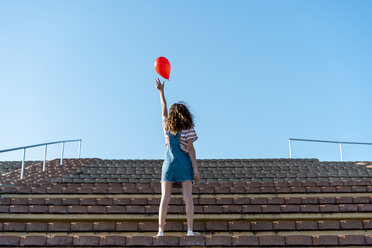 Young woman standing on granstand, letting go of a red ballon - AFVF02617