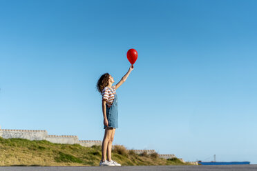 Young woman holding red ballon - AFVF02620