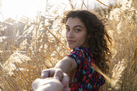 Young woman standing in meadow, holding hand of a young man - AFVF02623