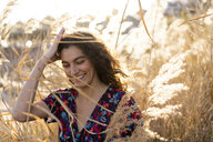 Portrait of a young woman standing in meadow, laughing - AFVF02629