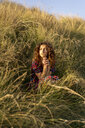 Pensive young woman crouching in meadow - AFVF02632