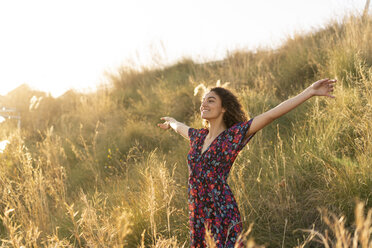 Happy young woman standing in summer meadow - AFVF02638