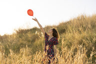 Happy young woman standing in summer meadow, letting go of a red balloon - AFVF02641