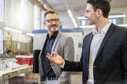 Two smiling businessmen talking in a factory - DIGF06223