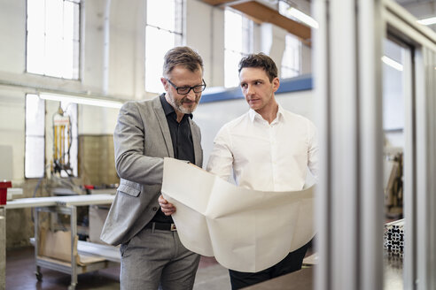 Two businessmen discussing plan in a factory - DIGF06226