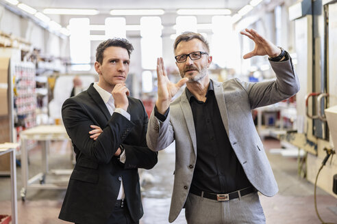 Two businessmen talking in a factory - DIGF06265