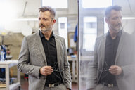 Portrait of businessman in factory thinking - DIGF06280