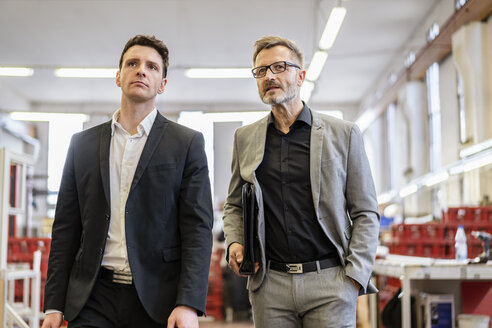 Two businessmen walking in a factory - DIGF06286