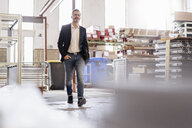 Businessman walking in factory warehouse - DIGF06301