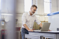 Businessman using laptop in factory - DIGF06310